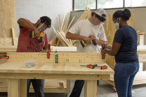 3 Building Construction student work with power tools to build a table