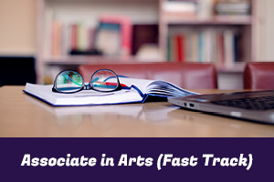 Associate in Arts (Fast Track): photo of a textbook, glasses and a laptop on a table