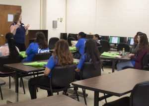 accounting instructor giving presentation to high school tour group