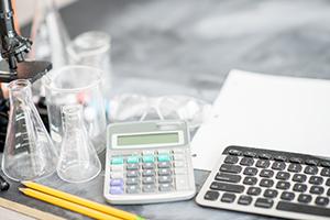 photo of a microscope, beakers, calculator and keyboard sitting on a desk